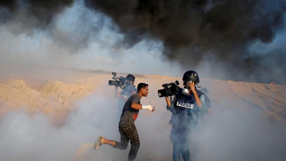 Cameramen film as a Palestinian demonstrator reacts to tear gas fired by Israeli troops during a protest calling for lifting the Israeli blockade on Gaza, on a beach near the maritime border with Israel, in the northern Gaza Strip. (Mohammed Salem / REUTERS)