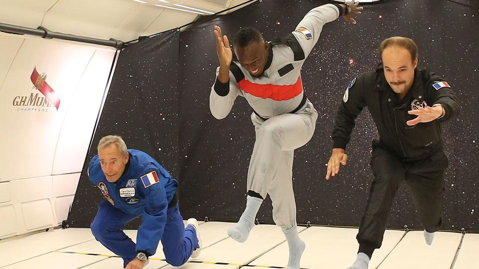 Jamaican retired sprinter Usain Bolt (C), French Interior designer Octave de Gaulle (R) and French former astronaut Jean-François Clervoy (L) in zero-gravity conditions in an aircraft above Reims during a promotional event for the Mumm Grand Cordon Stellar champagne designed to be drank by space tourists. (Laurent Theillet / Mumm / Novespace /AFP)