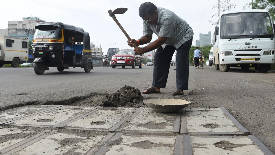 "Dadarao Bilhore fills up a pothole on the Western Express highway in Mumbai. The 48-year-old vegetable vendor does it to pay tribute to his son and in the hope that it will save lives. ""Prakash's sudden death left a huge void in our lives. I do this work to remember and honour him. ""I also don't want anyone else to lose a loved one like we have,"" Bilhore told AFP. (Indranil Mukherjee / AFP)"