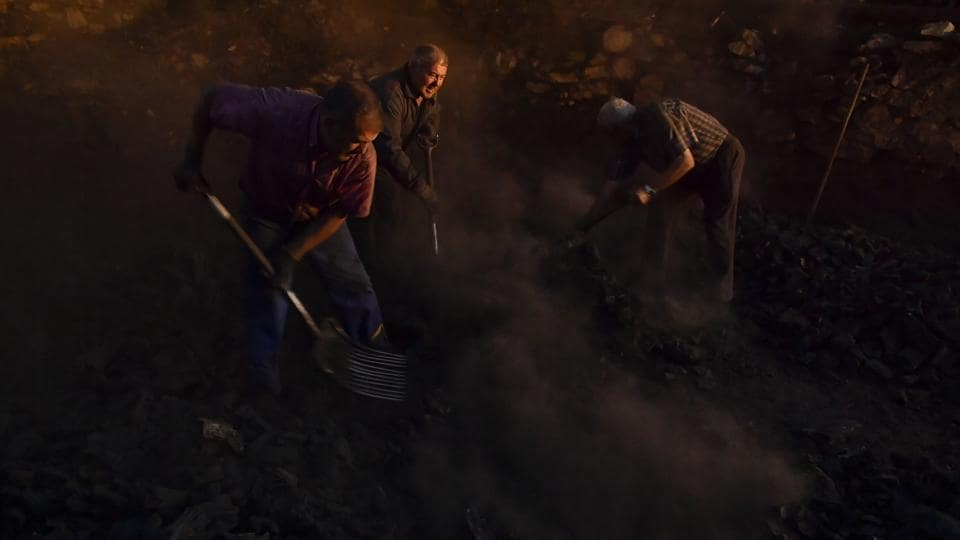 """Jesus Luis Remiro (C), picks up charcoal with his brother, Salvador (R), and Jose Mari Nieva (L), as part of a process to produce traditional charcoal in Viloria, northern Spain. Only a handful of professional """"charcoal cookers,"""" which is how locals call the back-breaking and patience exhausting process of turning firewood into lightweight pieces of carbon, remain active in Spain's northern Basque valleys. (Alvaro Barrientos / AP)"""