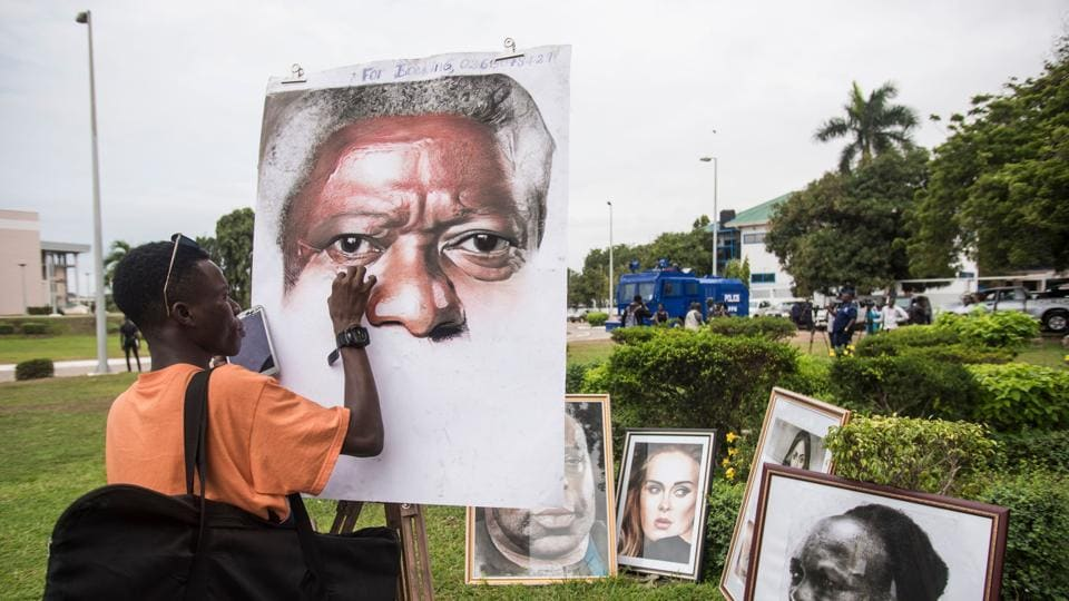 An artist paints a portrait of Kofi Annan at the entrance of Accra International Conference Centre in Accra, where the coffin of the Ghanaian diplomat and former Secretary General of United Nations who died on August 18 at the age of 80 after a short illness laid until his funeral. (Christina Aldehuela / AFP)