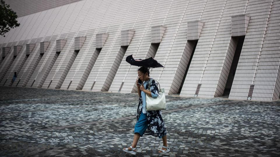 A woman uses an umbrella as she walks along a promenade that runs along Victoria Harbour in Hong Kong. (Anthony Wallace / AFP)