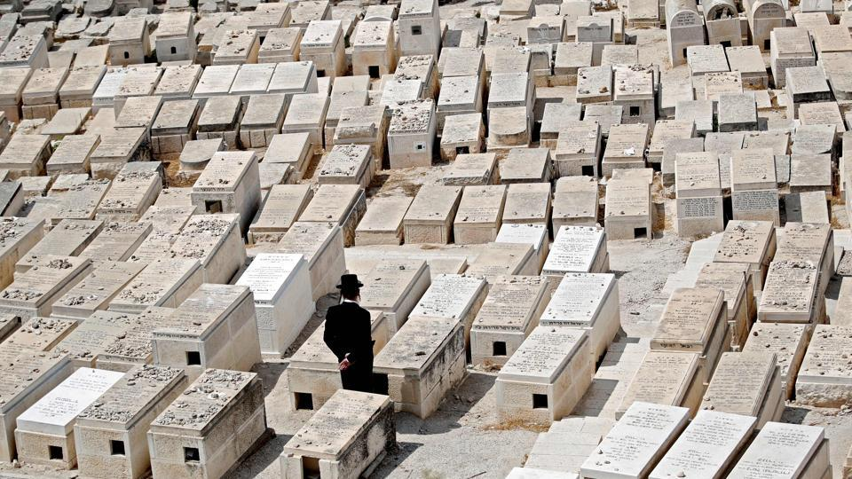 An Ultra Orthodox man mourns on tombs at the Jewish cemetery on the Mount of Olives in front of the Jerusalem's Old City. (Thomas Coex / AFP)