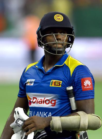 Sri Lanka's cricket team captain Angelo Mathews leaves the field after being dismissed by Bangladesh cricketer Rubel Hossain. (AFP)