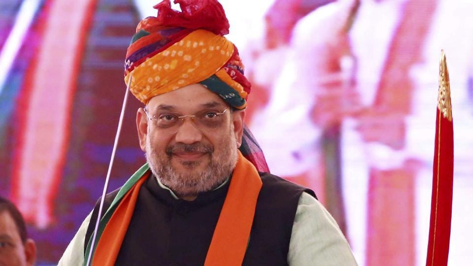 BJP president Amit Shah holds a sword presented to him at a rally of party workers during
