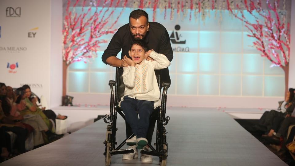 Designer Amit Aggarwal walks the ramp along with one of the students from Tamana.