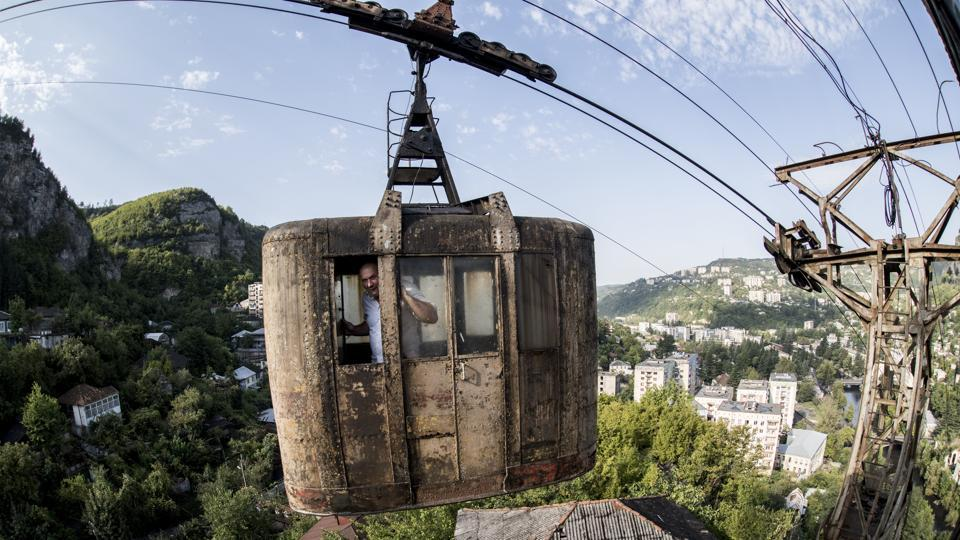 A local man looks through a window of a rusted cable car riding over the Georgian city of Chiatura, about 200 kilometers from Tbilisi, Georgia. The rusted, battered cable cars that hang hundreds of feet above this Georgian city could well be one of the world's scariest ways to commute to work or go shopping. (Evgeniy Maloletka / AP)