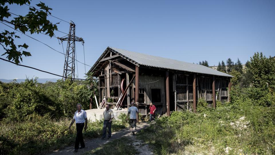 People near a cable car station in Chiatura. Some of the stations where the cars start and end are in semi-ruin, with chunks of masonry missing and their Soviet-era decorations fading. (Evgeniy Maloletka / AP)
