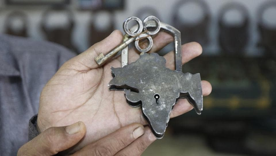 Dashrath Patel holds up a lock in the shape of undivided India, part of the Patel family collection in Hamirpura village, Kheda district, Gujarat. The family's collection of about 3,500 are a mix of originals and replicas. The heaviest weighs 41.5 kg and requires eight keys to open. The tiniest at 4 gm, and 1 inch high. (Nandan Dave / HT Photo)