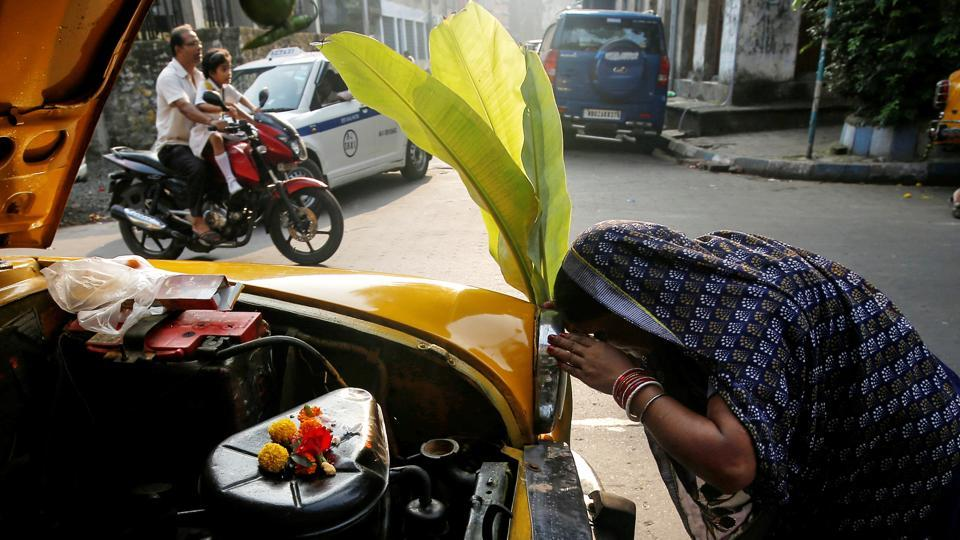 A taxi driver's wife offers prayers in front of their taxi during Vishwakarma Puja, a festival of the Hindu deity of architecture and machinery in Kolkata on Monday. Craftsmen believe that the creation of their tools was due to Vishwakarma, which is why on this day they worship the tools of their trade. (Rupak De Chowdhuri / REUTERS)