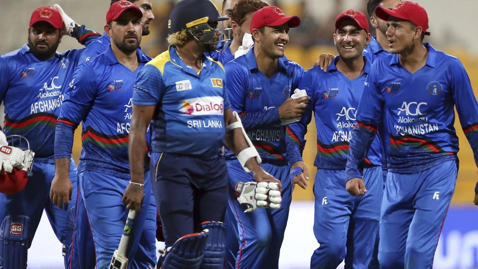Afghanistan's Mujeeb Ur Rahman, right, shares a light moment with Sri Lanka's Lasith Malinga, center wearing helmet, as they leave the field at the end of the one day international cricket match. (AP)