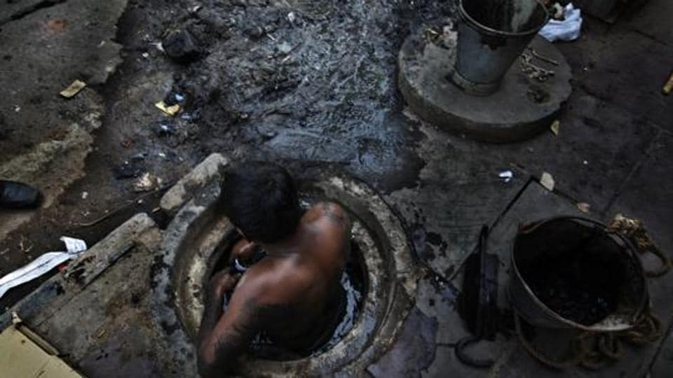 Municipal worker attempts to unblock a sewer overflowing with human excreta in New Delhi on October 7, 2009