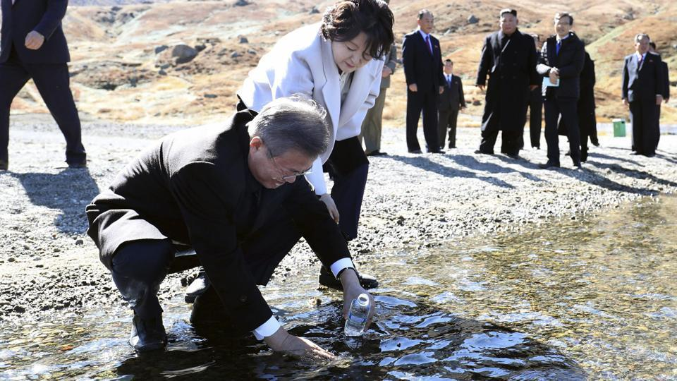 "South Korean President Moon Jae-in puts water from the crater lake into a bottle as his wife Kim Jung-sook looks on. The president has long stated that visiting Mount Paektu was a ""long unfulfilled dream."" ""Many people in the South would go to Mount Paektu from the China side, but I decided not to, pledging myself that I would go stepping on our soil,"" Moon told Kim after reaching the peak. (David Guttenfelder / AP)"