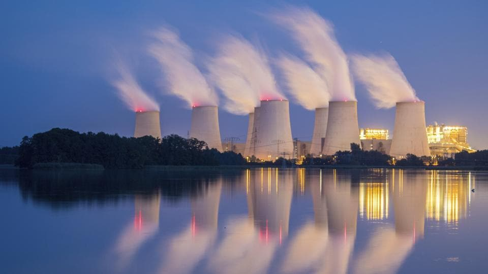 Steam and cooling towers of a lignite power plant are reflected in a pond in Peitz, eastern Germany. (Patrick Pleul / dpa via AP)