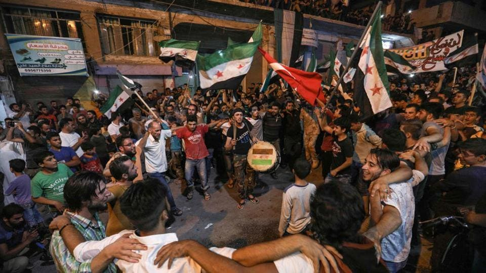 Syrians dance, chant slogans and strike drums while others wave flags of Turkey and the opposition, as they protest against the Syrian government during a demonstration in Binnish in the rebel-held northern Idlib province. (Omar Haj Kardour / AFP)