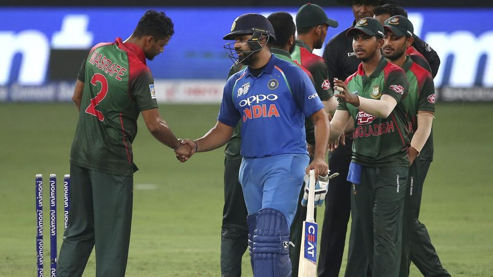 Rohit Sharma, holding bat, shakes hands with Bangladesh's captain Mashrafe Mortaza, left, as he leaves the field. (AP)