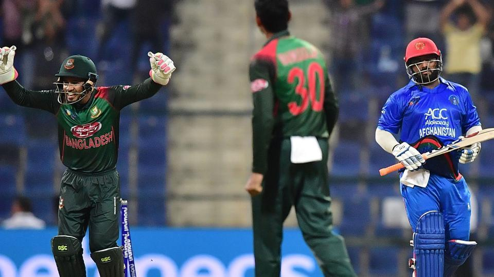 Afghanistan batsman Mohammad Shahzad (R) leaves the pitch after being dismissed during the one day international (ODI) Asia Cup cricket match between Afghanistan and Bangladesh at The Sheikh Zayed Stadium in Abu Dhabi.