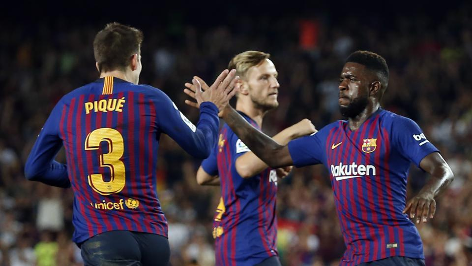 Barcelona's French defender Samuel Umtiti (R) congratulates Barcelona's Spanish defender Gerard Pique for his goal during the Spanish league football match between FC Barcelona and Girona FC at the Camp Nou