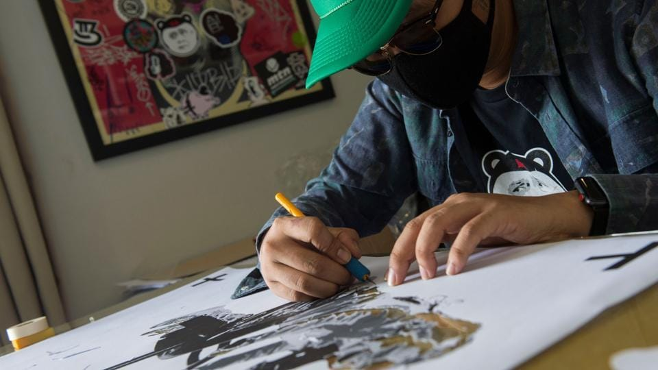 """A Thai artist who goes by the name of 'Headache Stencil' works in his studio in Bangkok. Dubbed Thailand's """"Banksy"""", Headache -- whose nickname alludes to the pain he hopes to inflict on the mighty -- catapulted to fame in January with a piece skewering junta number two Prawit Wongsuwan, who was struggling to explain his collection of undeclared luxury watches. (Romeo Gacad / AFP)"""