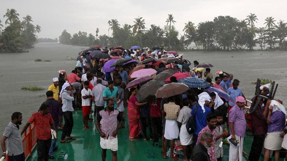 Volunteers use umbrellas to protect from rain as they cross Pampa river to reach to flood-affected areas to clean houses and public places following floods in Kuttanad in Alappuzha district of Kerala.