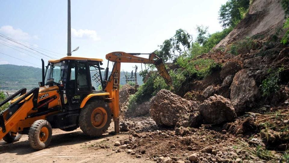 A JCB machine clears debris from a road after a landslide took place on the outskirts of Jammu on Tuesday. Thirty people, including women and children were rescued in Jammu and Kashmir during a flash flood in Kathua district on Monday. These people were marooned in different parts of the district following heavy rains. (Nitin Kanotra/HT)