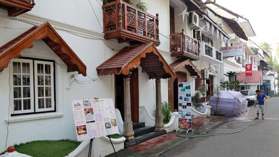 A worker cleans the entrance of a hotel, next to the signboard for OYO Rooms at Fort Kochi, Kerala.