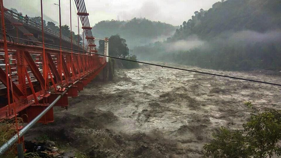 A damaged bridge is seen as flood water gushes into Ravi river during rainfall, in Chamba, on Tuesday. The Indian Meteorological Department (IMD) Tuesday predicted dry weather for Himachal Pradesh from Wednesday onwards, a day after downpours killed 25 people in flashfloods, landslides, roof-collapse and other incidents triggered by incessant rain in north India. Traffic halts on roads leading to Kedarnath, Badrinath temples due to landslides at multiple places since Monday. (PTI)