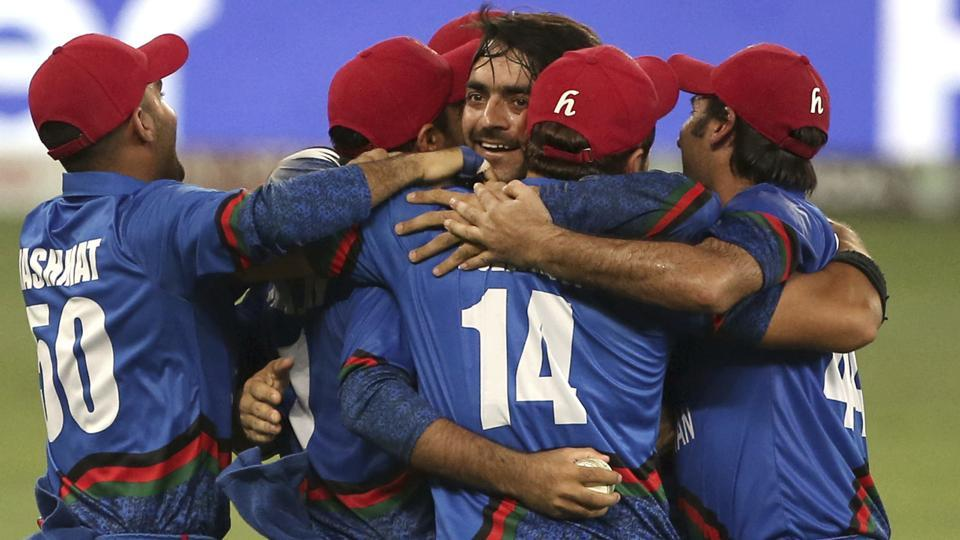 Afghanistan players congratulate teammate Rashid Khan, center without cap, after he dismissed India's Ravindra Jadeja during the one day international cricket match of Asia Cup between India and Afghanistan in Dubai. (AP)