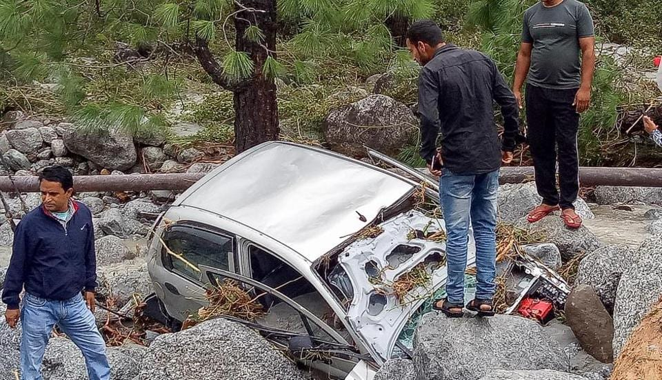 Locals inspect a damaged car washed ashore due to incessant rains, at Palampur approximately 45km from Dharamshala, Monday, Sept 24, 2018.