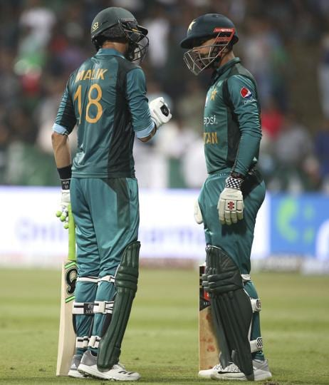 Pakistan's Shoaib Malik, left, gives some tips to teammate Shadab Khan as he leaves the ground after losing his wicket. (AP)