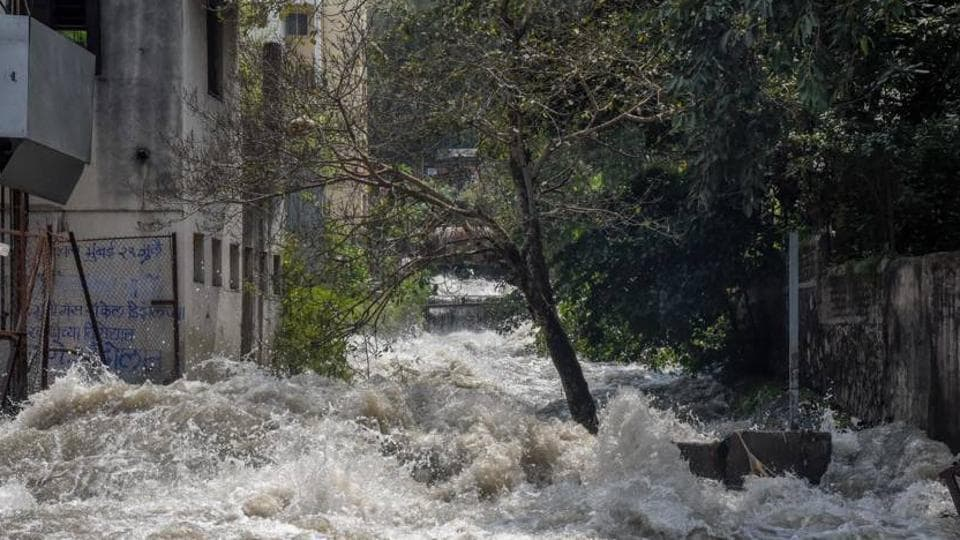Water floods the residential area near Dandekar bridge after the canal wall was breached on Thursday morning.