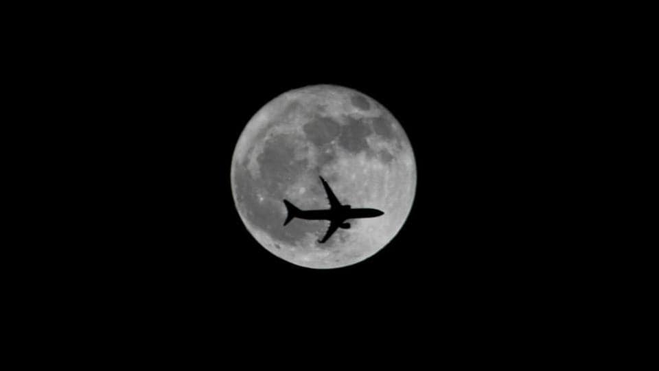 A passenger plane passes the moon as it comes in to land at the international airport in Chennai, Tamil Nadu. (P. Ravikumar / REUTERS)