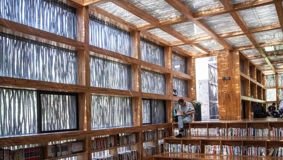 Deep in the heart of a valley surrounded by rocky hills, a wooden library sits just over a creek on the outskirts of Beijing, seemingly in the middle of nowhere. (Fred Dufour / AFP)