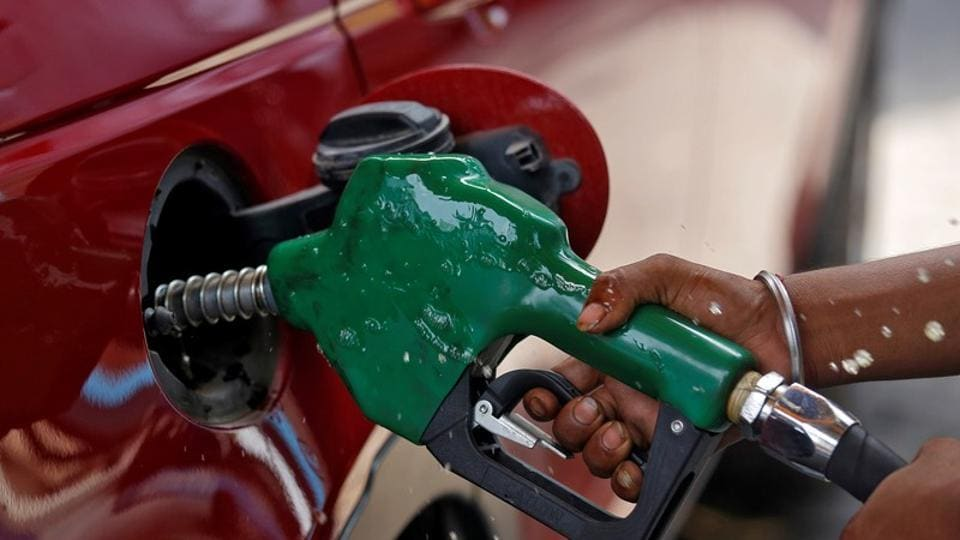 A worker holds a nozzle to pump petrol into a vehicle at a fuel station in Mumbai.