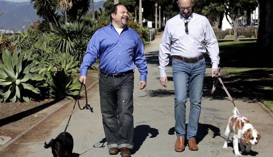 Steven May (right) walks with his dog, Winnie, beside his attorney, David Pisarra, with his dog, Dudley in Santa Monica, California.