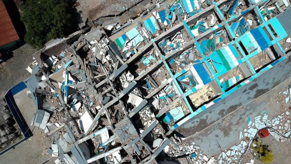 This aerial picture shows the remains of a ten-storey building in Palu in Indonesia's Central Sulawesi on September 30, 2018 after it collapsed following a strong earthquake in the area.