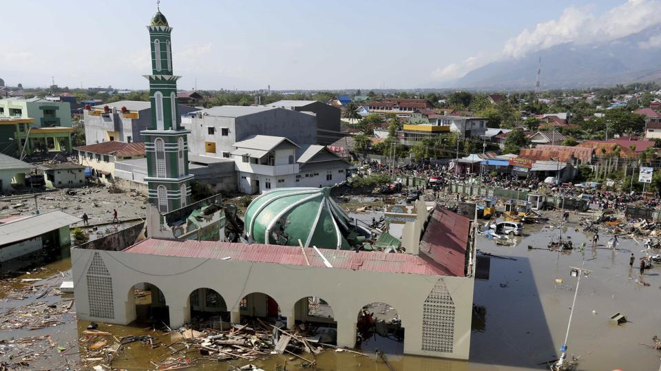 People survey a mosque damaged during a earthquake and a tsunami in Palu, Indonesia. The death toll, which has more than doubled from Sunday morning, is expected to climb higher still, with heavily populated areas outside the city still cut off from any assistance, and desperate search-and-rescue efforts continuing in the rubble of Palu, often with only rudimentary tools. (Tatan Syuflana / AP)
