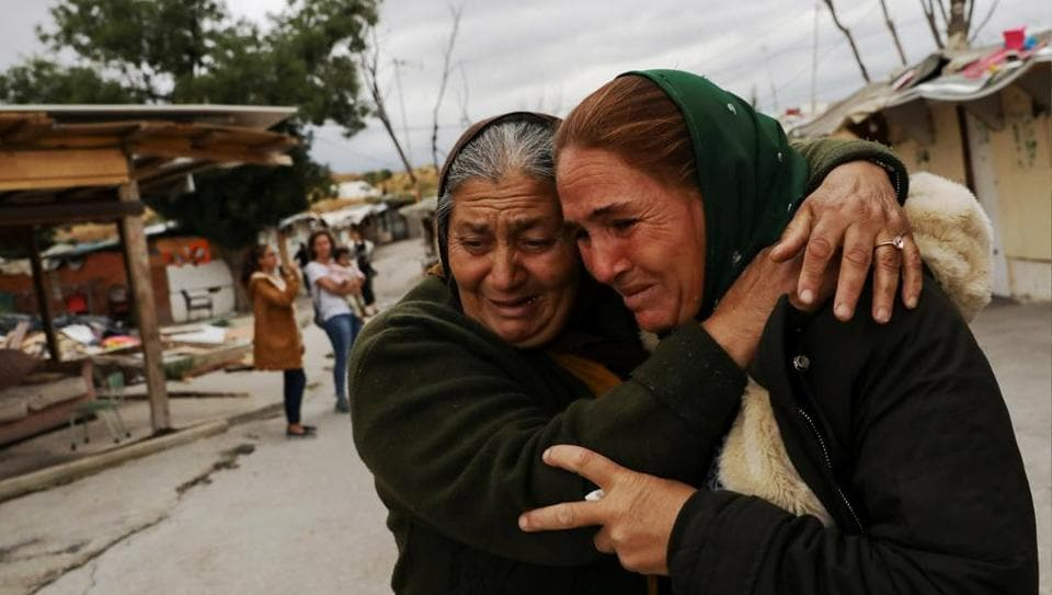 """Ramona Stan, 41, is comforted by a neighbour as she leaves El Gallinero shanty town to relocate to a new apartment in Madrid, Spain. A makeshift camp dubbed the """"Gallinero"""" was demolished on the outskirts of Madrid last week and its 150 Roma residents offered alternative accommodation. But for those who have known little else, the change is daunting. (Susana Vera / REUTERS)"""