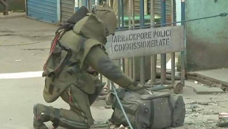 A bomb disposal expert inspects a bag at the Dumdum marketplace where an improvised explosive was set off on Tuesday morning.