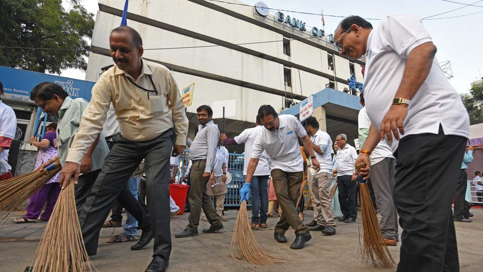 Staff members of the Bank of Maharashtra participate in a cleanliness drive on the eve of Gandhi Jayanti in Pune on Monday. (Pratham Gokhale/HT Photo)