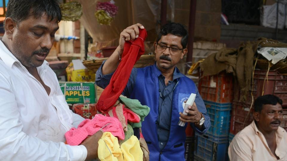 A shopkeeper (L) holds cloth bags while a city civic officer (C) checks them. A walk through Crawford Market and visits to grocery stores and food stalls suggest many traders have switched to cloth bags and paper straws. But others continue to violate the ban and large piles of plastic items can still be seen on the city's beaches and streets. (Punit Paranjpe / AFP)