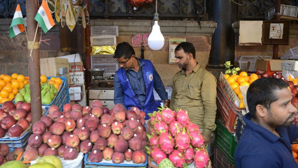 A city civic officer (L) inspects a fruit stall for unauthorised plastic bags at a wholesale market in Mumbai. Members of the blue squad say they are too small in number to rid Mumbai of all its plastic, but are determined to do what they can. (Punit Paranjpe / AFP)