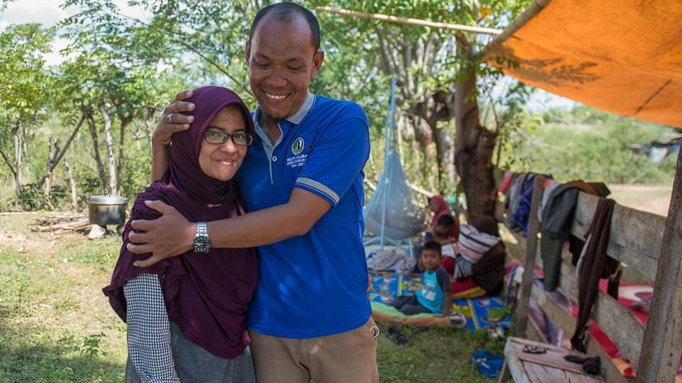 Azwan hugs his wife Dewi Prasasti in front of their house and family members in Palu, Central Sulawesi, after an earthquake and tsunami hit the area on September 28.