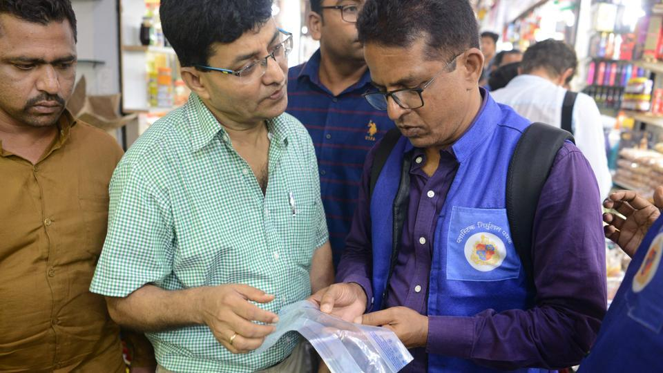 "A city civic officer (in blue) explains restrictions on plastic bag usage to shopkeepers. Wearing matching blue Nehru jackets, a dozen inspectors fan out across Mumbai's hectic Crawford Market, each scouring for violators of an ambitious plastic ban. Among them is Mahindra Wayangankar, 50, one of 311 officials dubbed the ""blue squad"" and tasked with enforcing a recent ban on single-use plastics in the country's commercial capital. (Punit Paranjpe / AFP)"