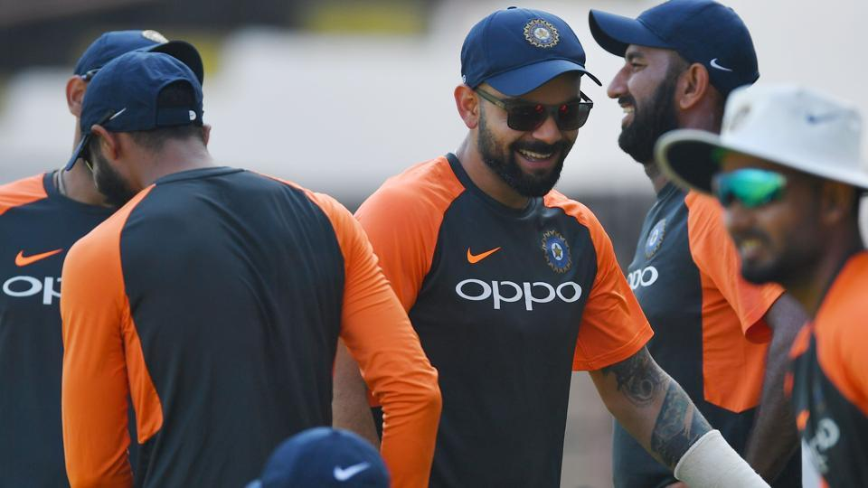 Indian cricket captain Virat Kohli (C) jokes with teammates as he arrives for a training session. (AFP)