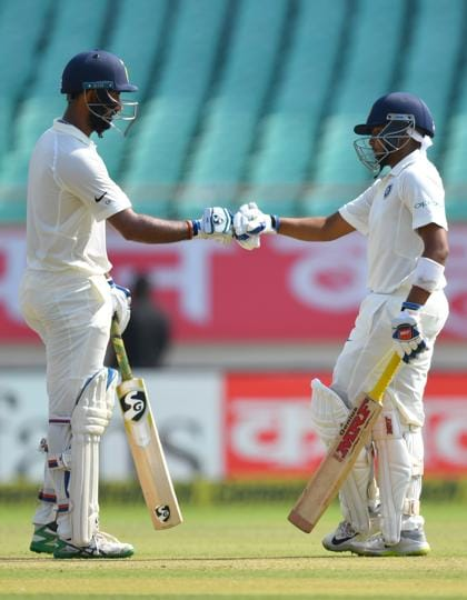 India's batsmen Cheteshwar Pujara (L) and Prithvi Shaw touch fists during the first day's play of the first Test cricket match between India and West Indies at the Saurashtra Cricket Association stadium in Rajkot. (AFP)