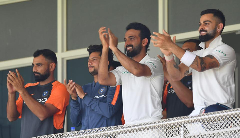 Indian cricketers (L-R) Mohammed Shami, Kuldeep Yadav, Ajinkya Rahane and Virat Kohli aplaud after teammate Prithvi Shaw scored a century (100 runs) during the first of the first Test cricket match between India and West Indies at the Saurashtra Cricket Association stadium in Rajkot. (AFP)