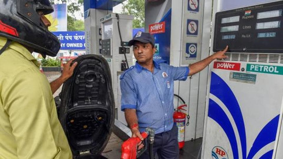 An employee shows the revised prices of petrol and diesel to a customer at a fuel station in Mumbai.