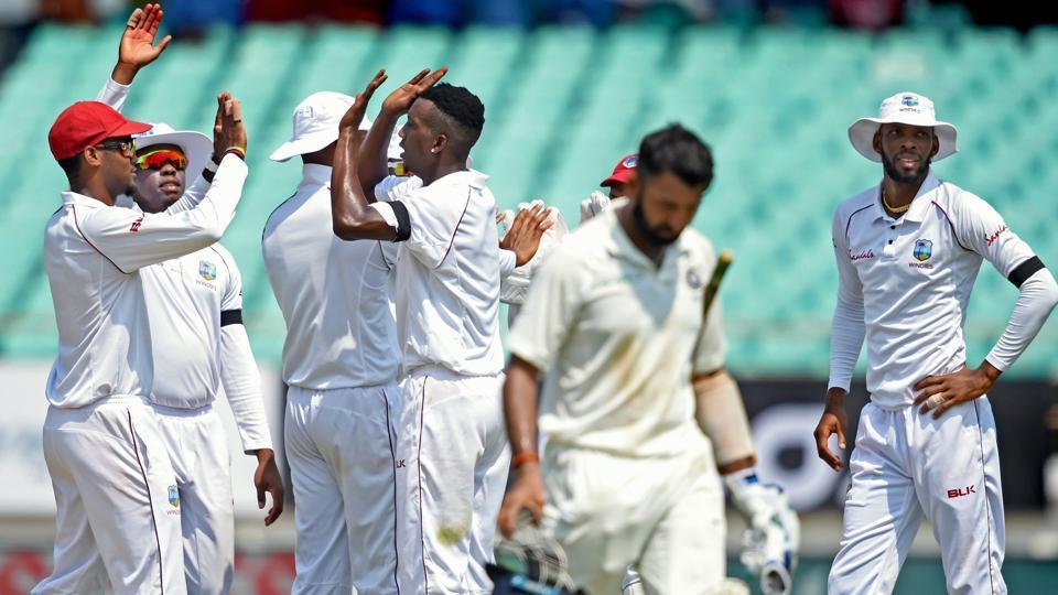 West Indies bowler Sherman Lewis celebrates the dismissal of Indian batsman Cheteshwar Pujara on day one of the first test cricket match against West Indies, in Rajkot. Virat Kohli scored a brilliant half century and his partnership with Ajinkya Rahane has taken India's score beyond 300 on the day one of the test match. (PTI)