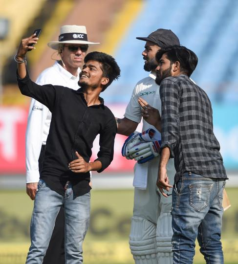 Rajkot: Indian batsman Virat Kohli interacts with his fans who forced their way into the field to take a selfie with the player during the ongoing test cricket match played between India and West Indies in Rajkot (PTI)